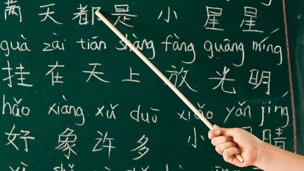 Someone pointing at Chinese characters on a chalkboard