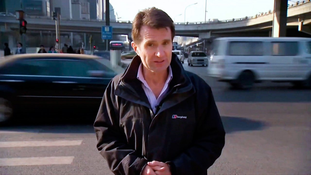 David Shukman, Science Editor, BBC News, standing in front of a road.