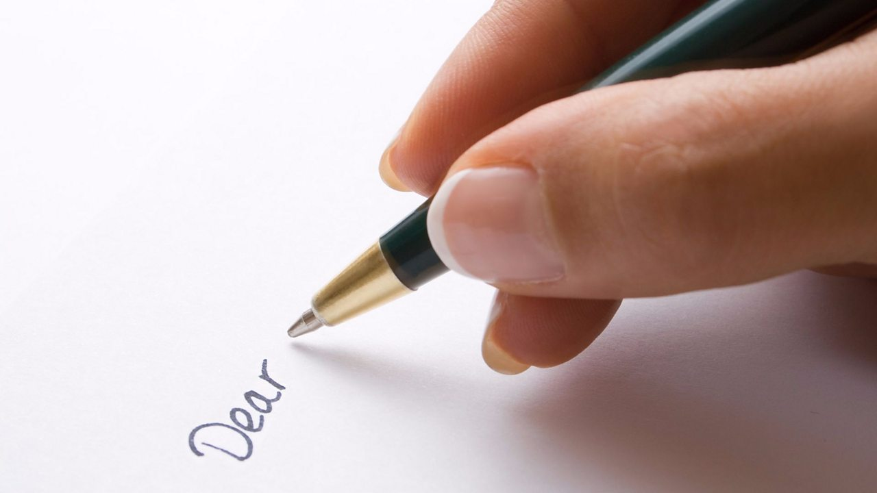 A hand holds a pen, the word 'Dear' is written on a piece of paper