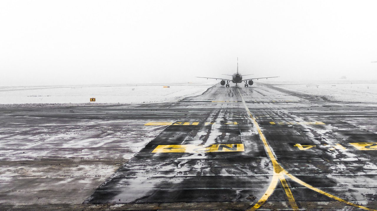 An airport runway in snow and fog