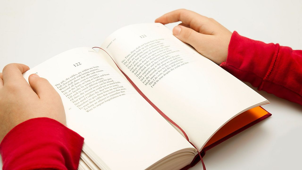 Hands hold open a book of Shakespeare's sonnets showing 14 lines per sonnet