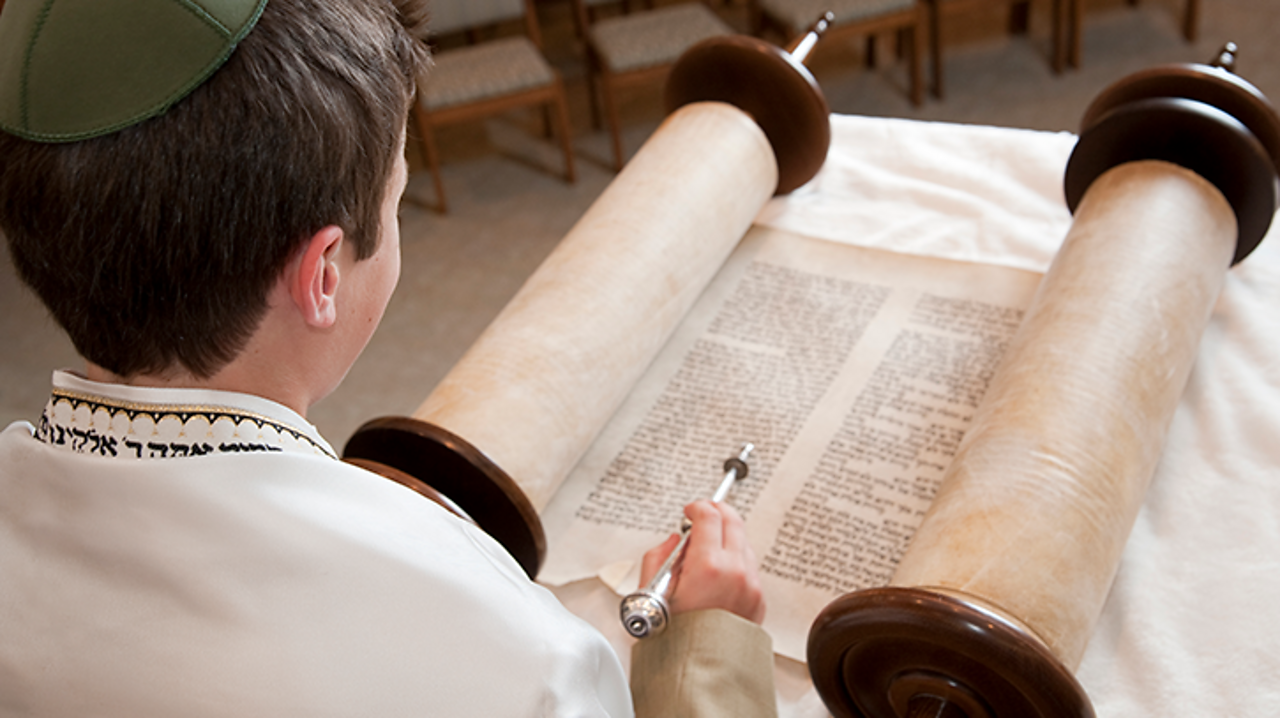 These are the Torah scrolls being read by a boy during his Bar Mitzvah ceremony in a synagogue. The scrolls are wrapped around wooden handles. He is using a yad to follow the words.