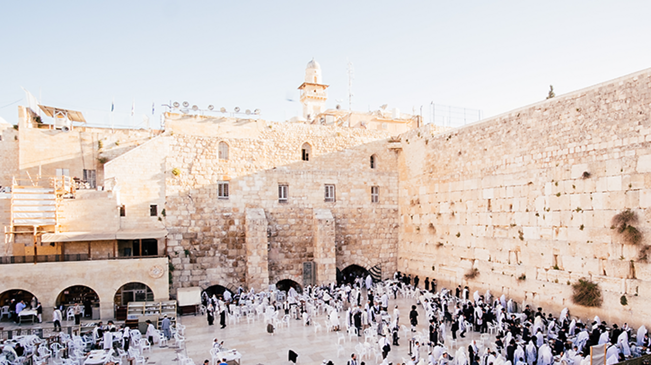 This is the Western Wall in the Old City of Jerusalem in Israel. It is a huge ancient wall made of limestone and it is the holiest place that Jews are allowed to pray. Lots of people pilgrimage here every year to pray at the foot of the wall. This is why it is sometimes called the Wailing Wall.