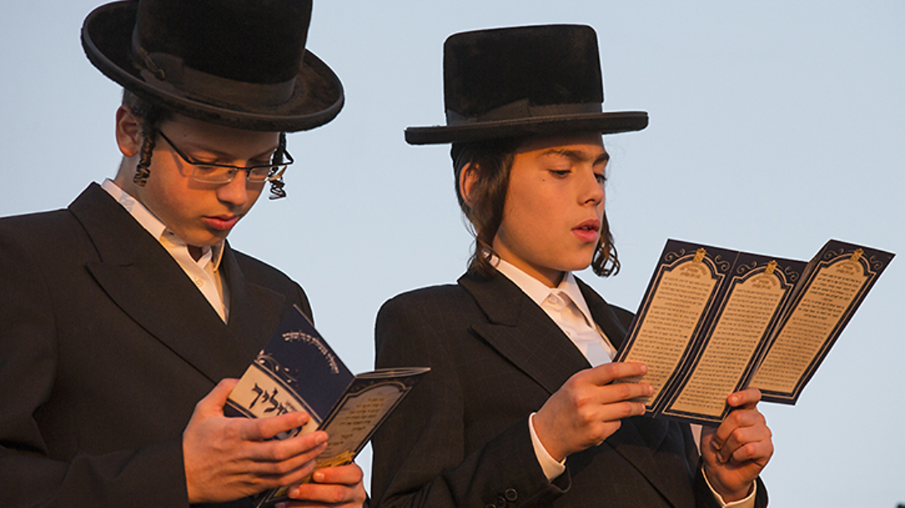 These are two Orthodox Jews from Israel. Orthodox means they follow a stricter form of Judaism than other progressive or liberal Jews. They have long side-burns which are called Payot.