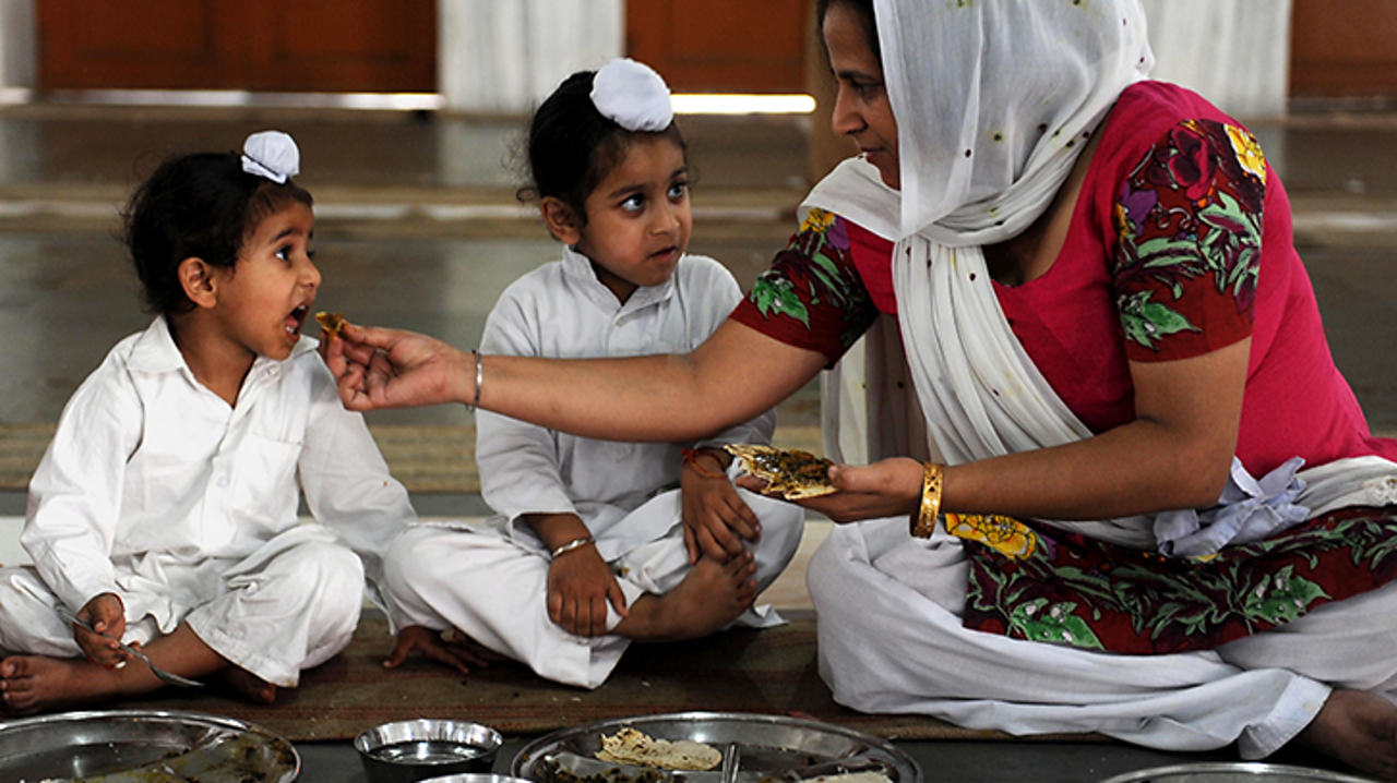 Two young Sikhs are being fed by their mother