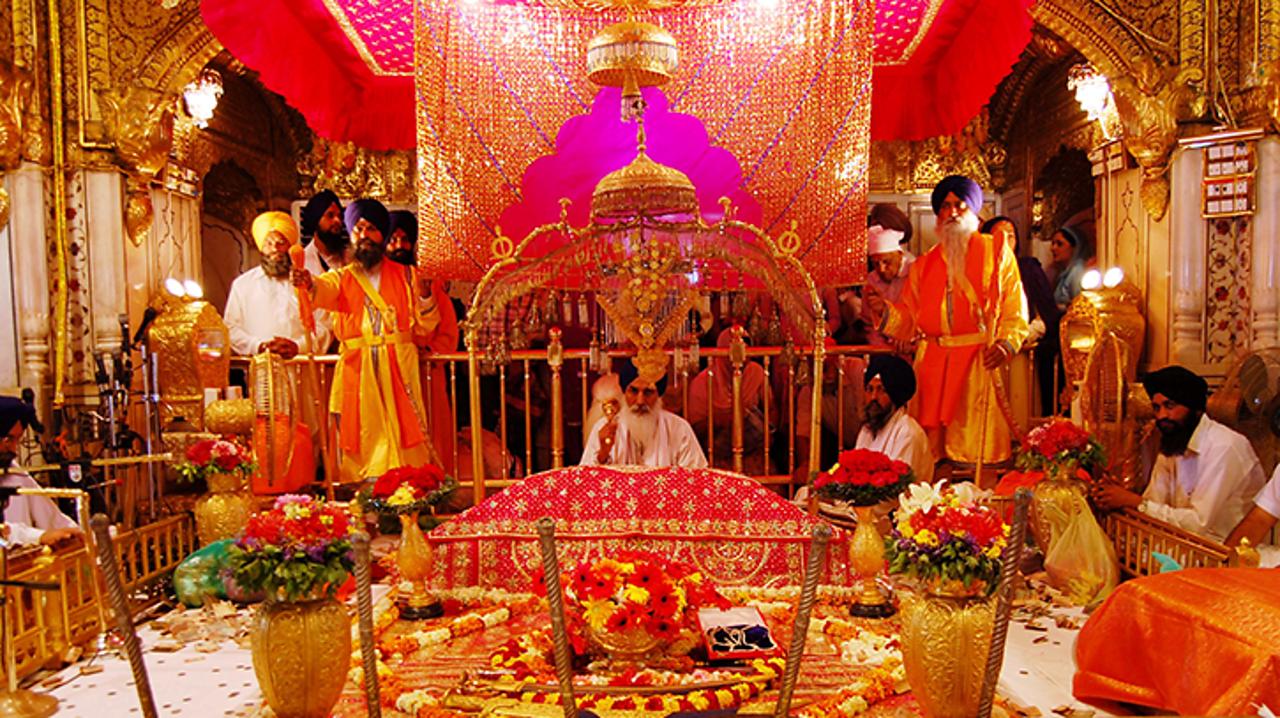 A Sikh priest sits behind the Guru Granth Sahib holy book in the Gurdwara