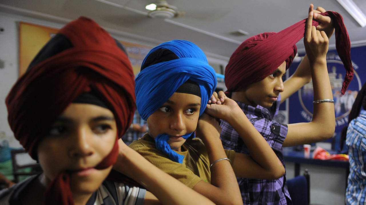 These Sikhs are practicing tying their turbans.
