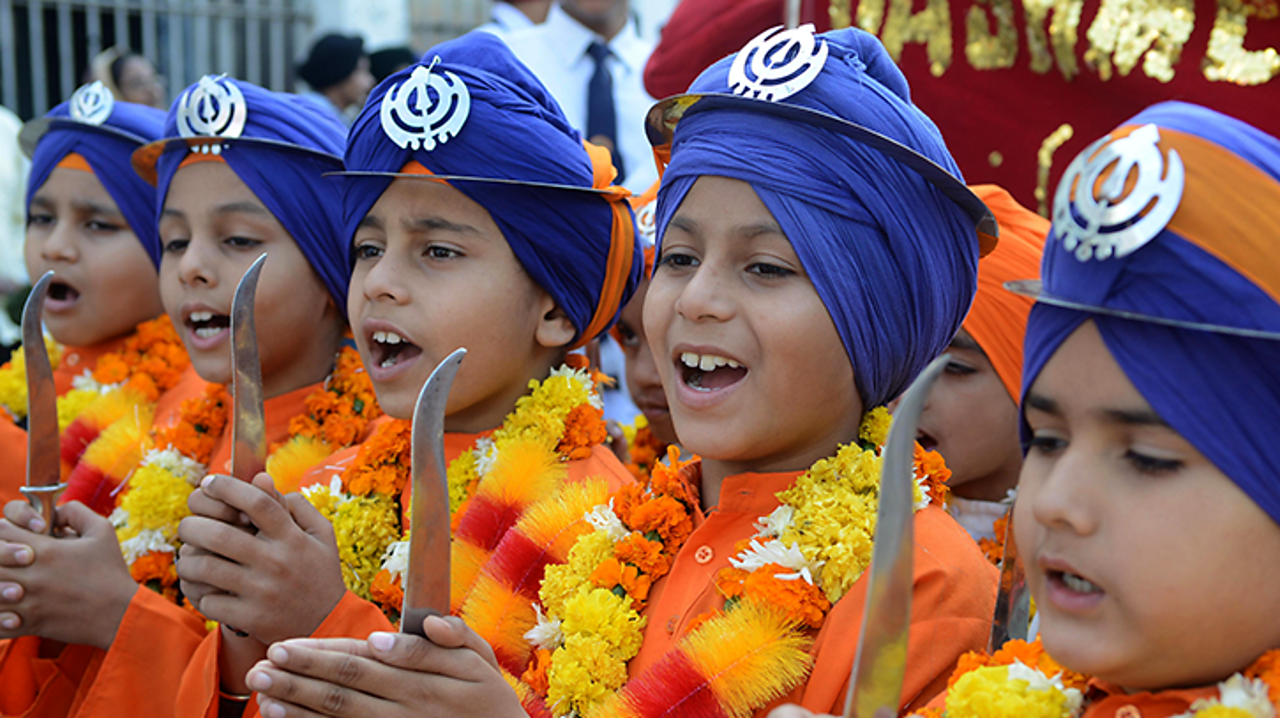 These Indian Sikh's are dressed as Panj Pyare. They are marching in a procession celebrating one of the Sikh Gurus' birthday.