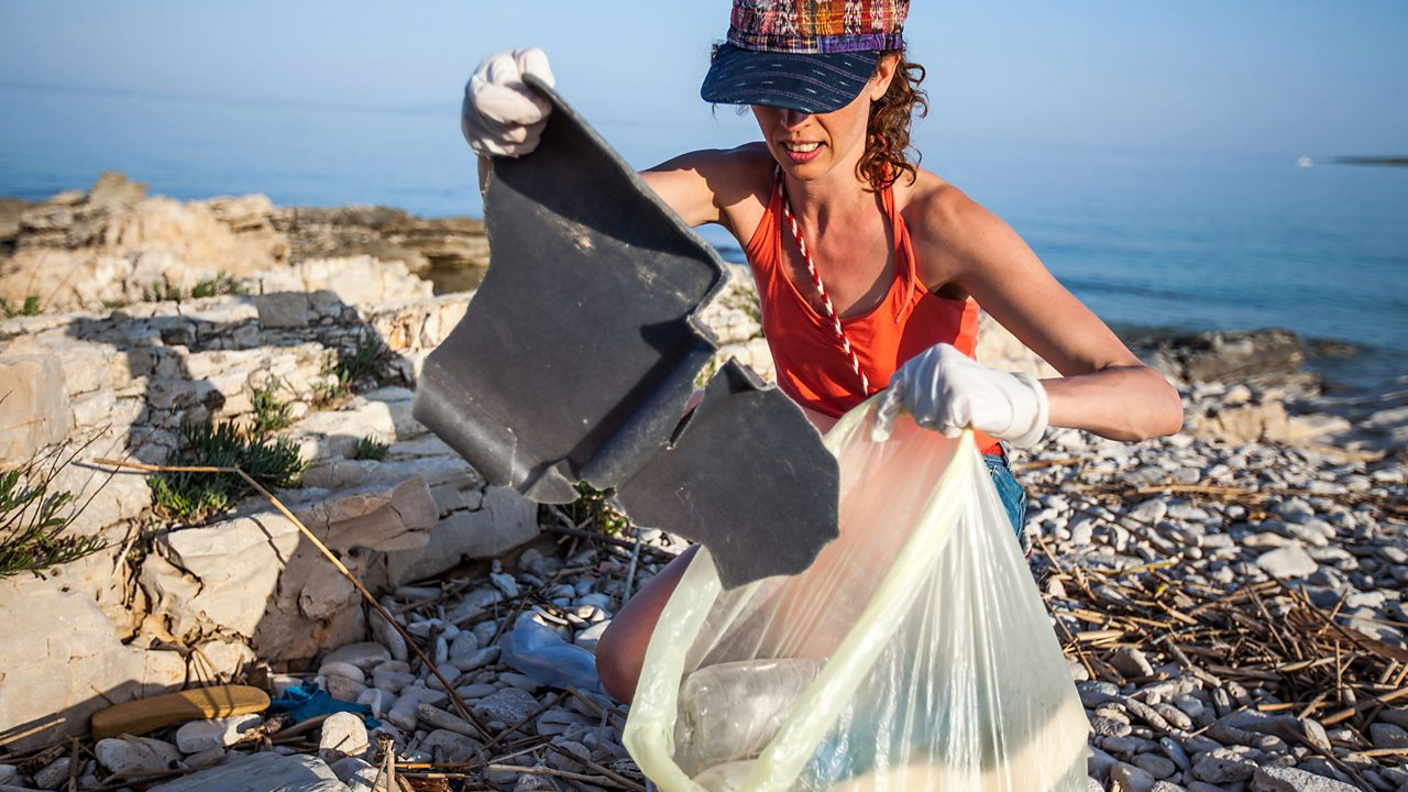 Picking up plastic on a beach: if we don't dispose of plastic properly, then it can sometimes end up in the sea and wash up on beaches.