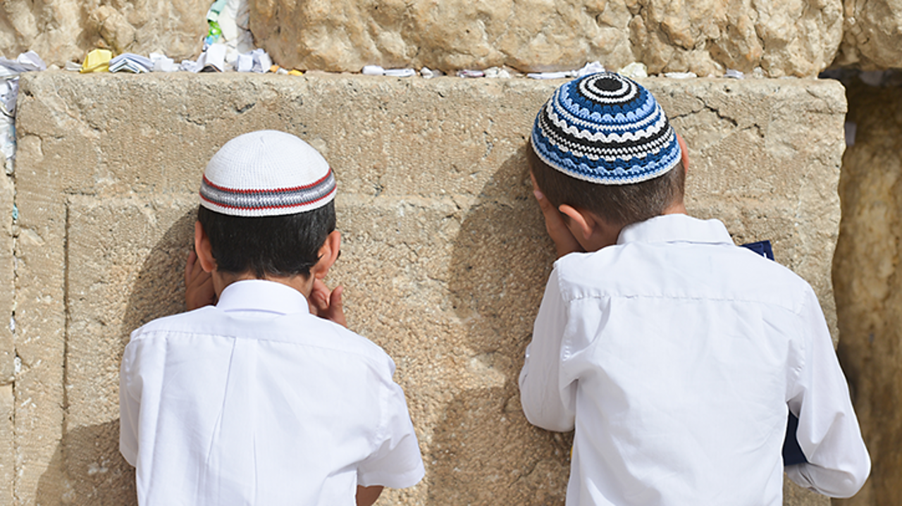 These two boys are praying at the Western Wall in Jerusalem. They are both wearing a brimless cap called a kippah.