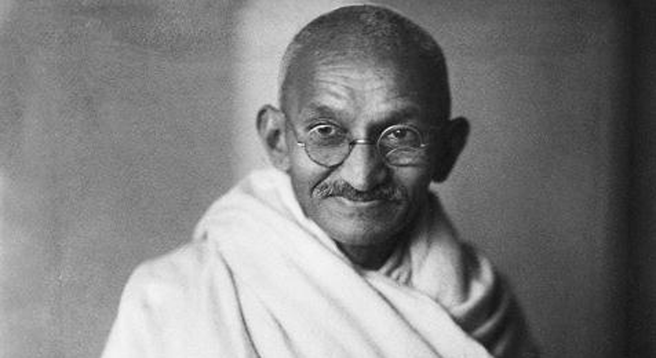 Black and white photograph of Ghandi in simple white cloth clothes
