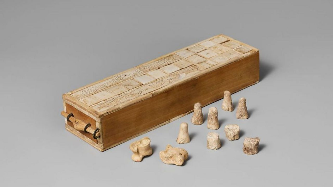 A photo of an ancient Egyptian game box with playing pieces and knuckle bones for dice