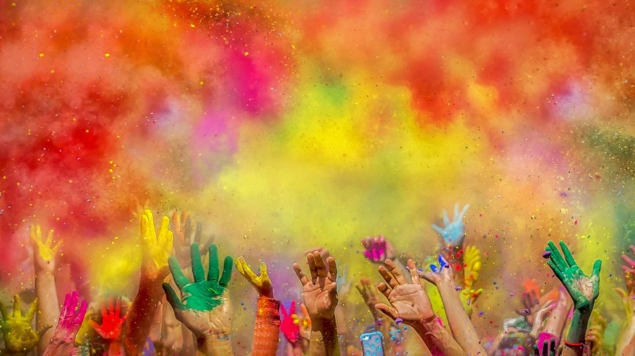 Coloured gulal powder being thrown at Holi festival