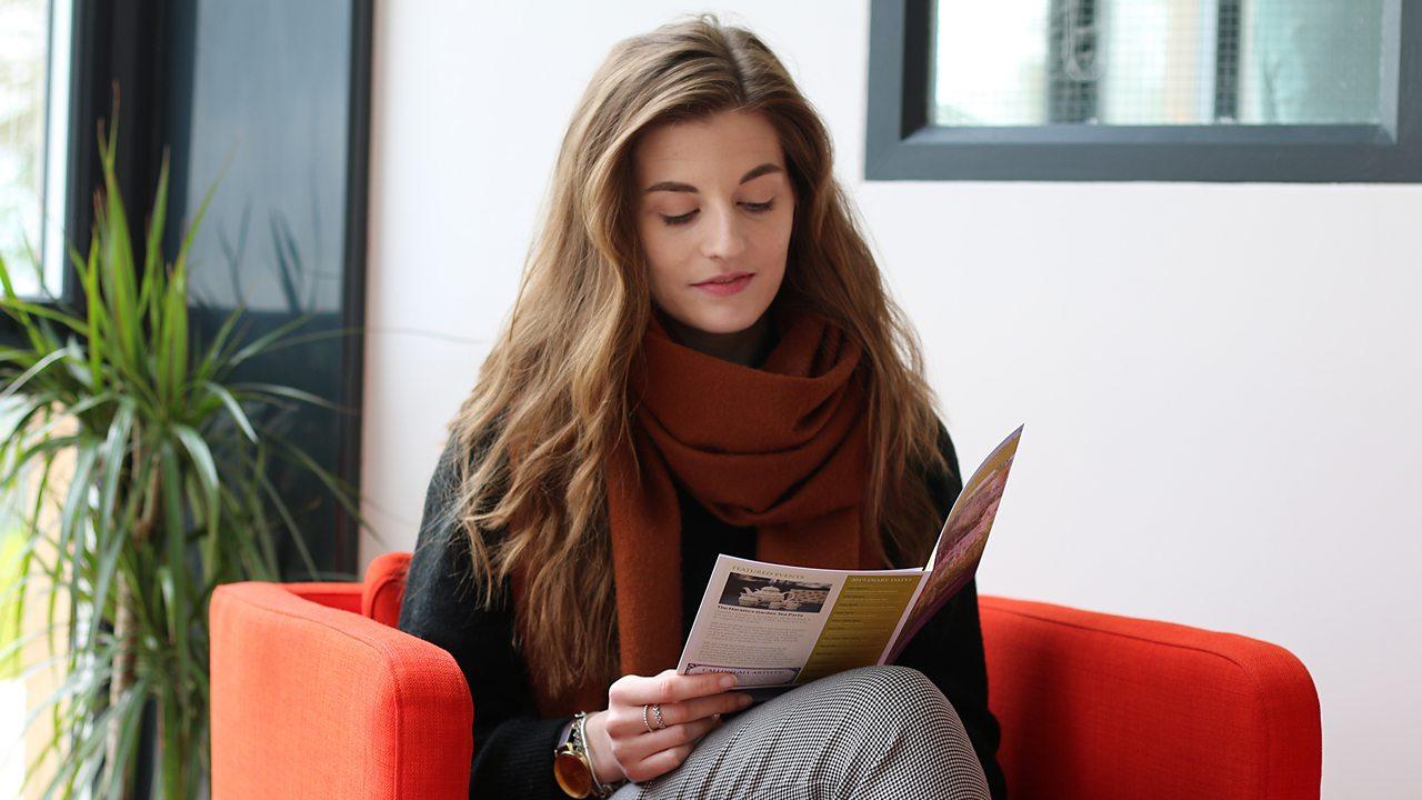 Alex reading a leaflet.