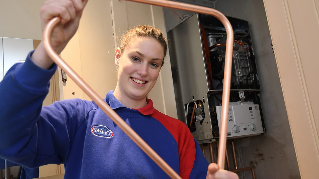 Sophie holding some copper pipe.