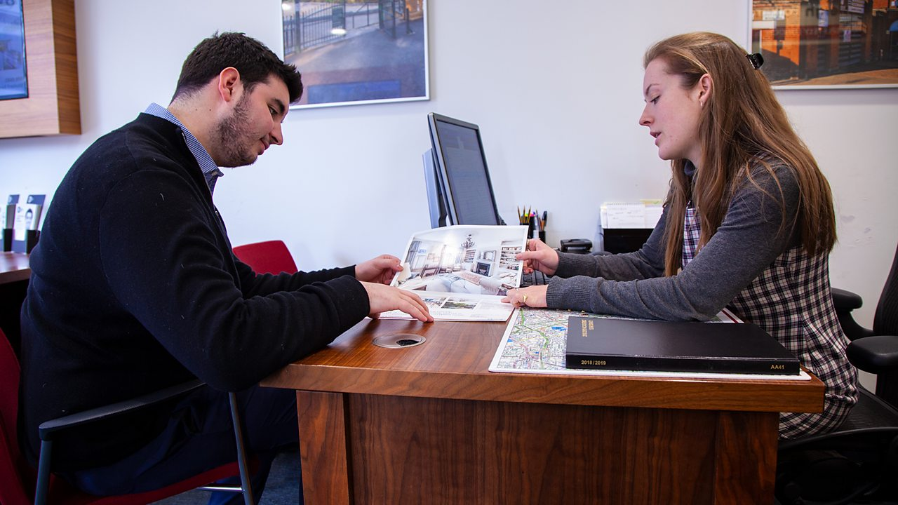 Samantha showing a property brochure to a client.