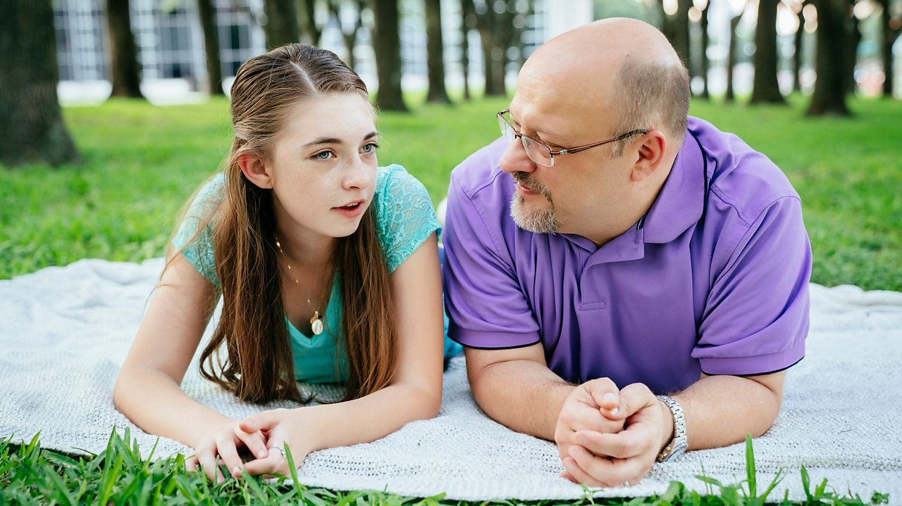 Father and daughter having a conversation in a park