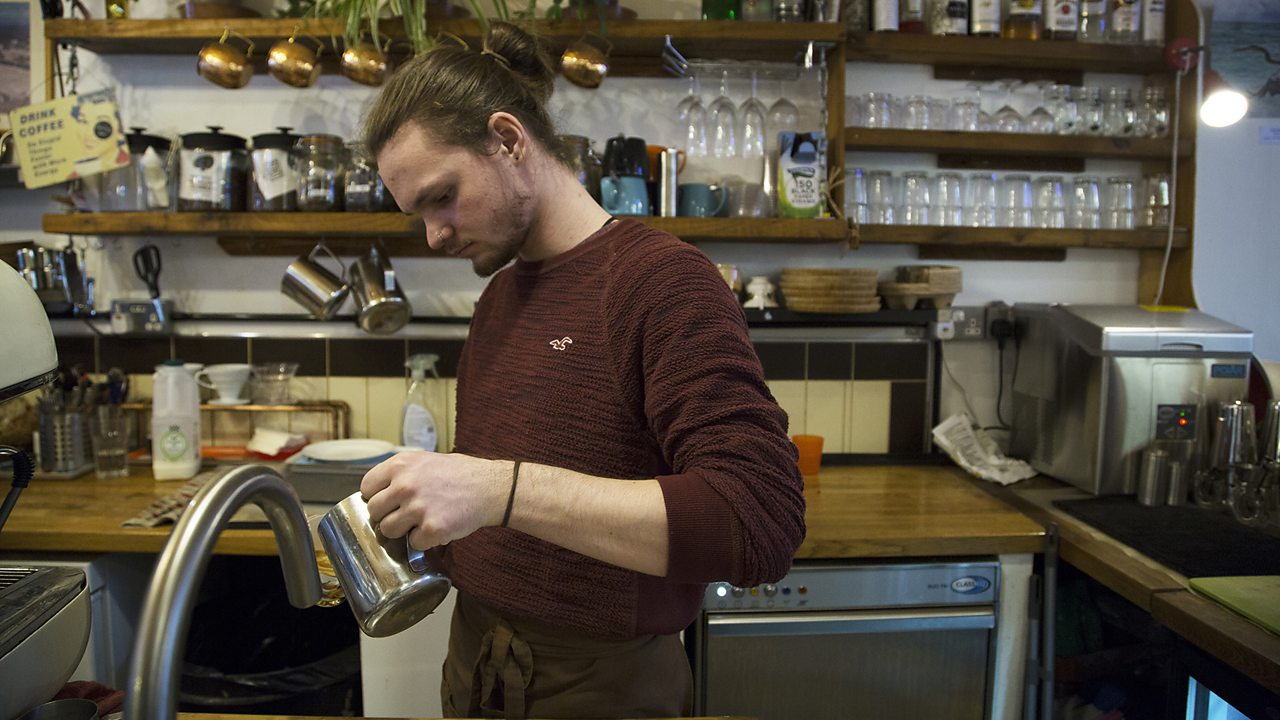 Zach pouring a drink in the coffee shop.