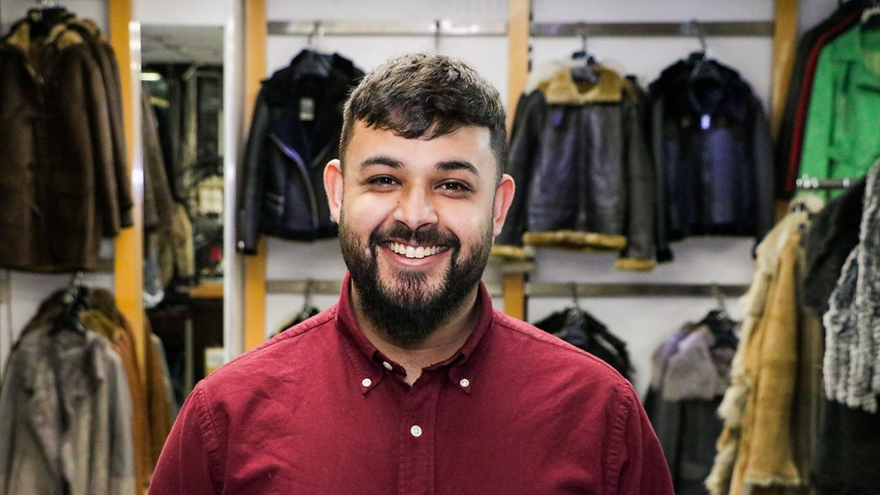 Wasim in the shop, smiling at the camera.