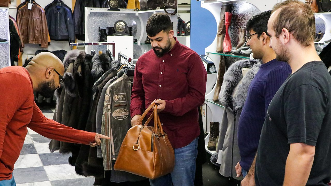 Wasim and his colleagues, looking at one of their products – a brown leather bag.
