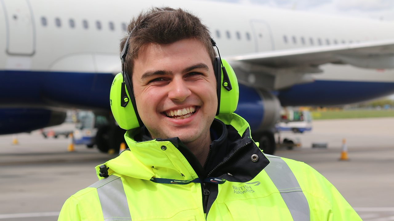 Alex at the airport wearing safety clothing and noise cancelling headphones.