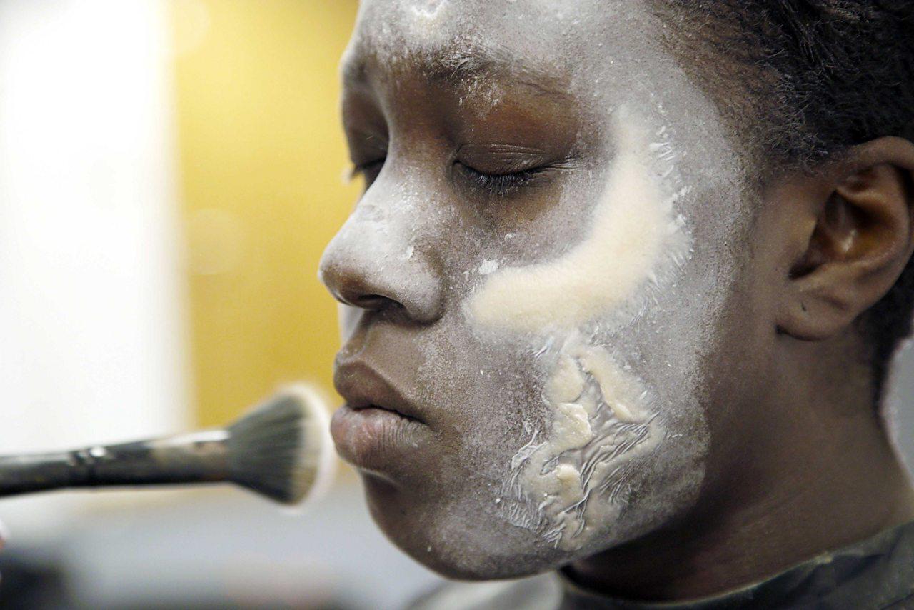 Amrita applying makeup to a model.