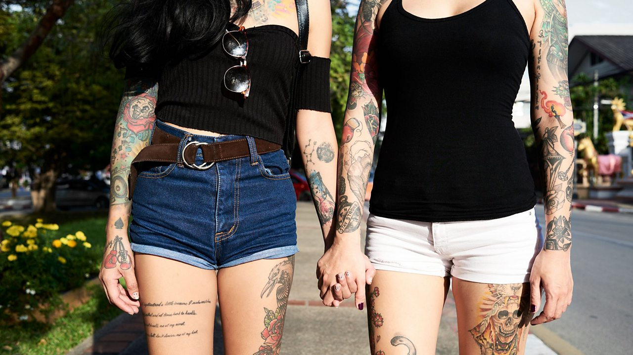 a tattooed couple hold hands in the street