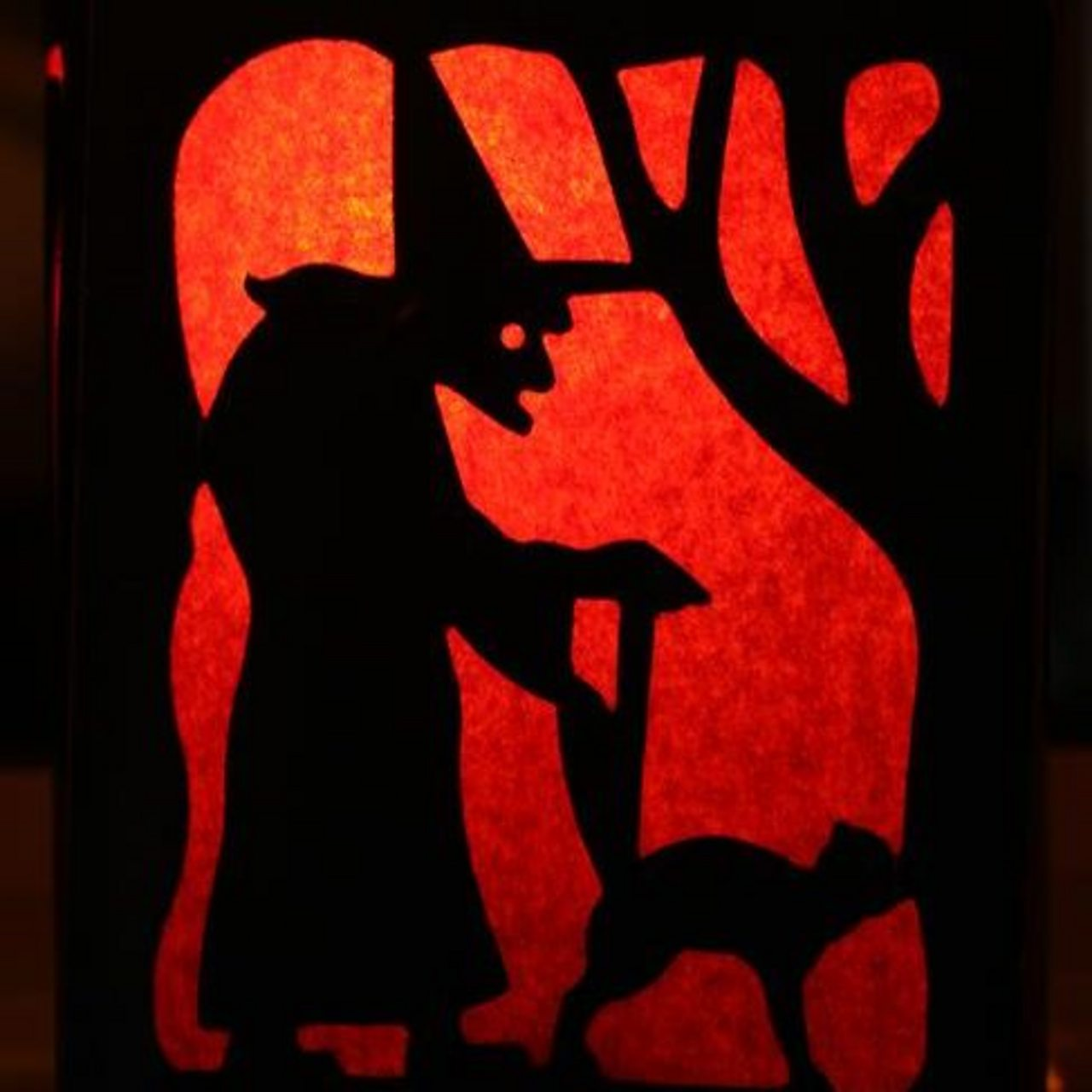 A silhouette of a witch with a pointy hat with a cat by her feet