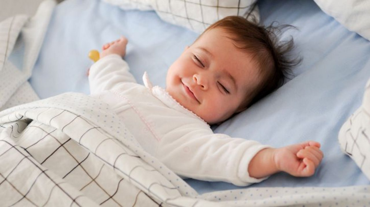A baby sleeping with a big smile on their face.