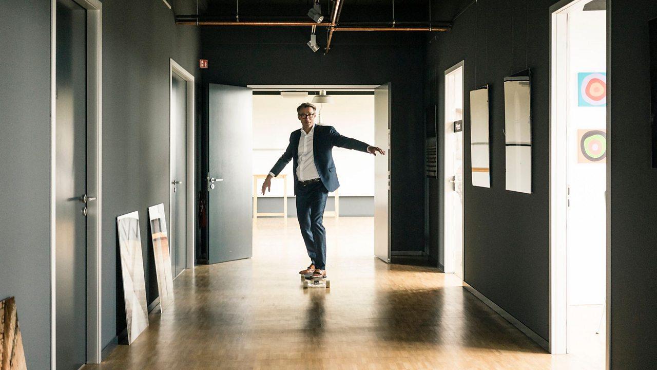 A man in smart clothes skateboarding down an empty school corridor.