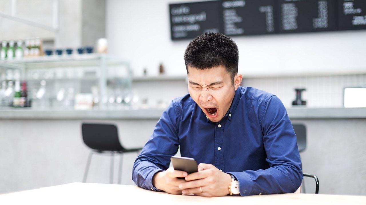Man yawning looking at his phone