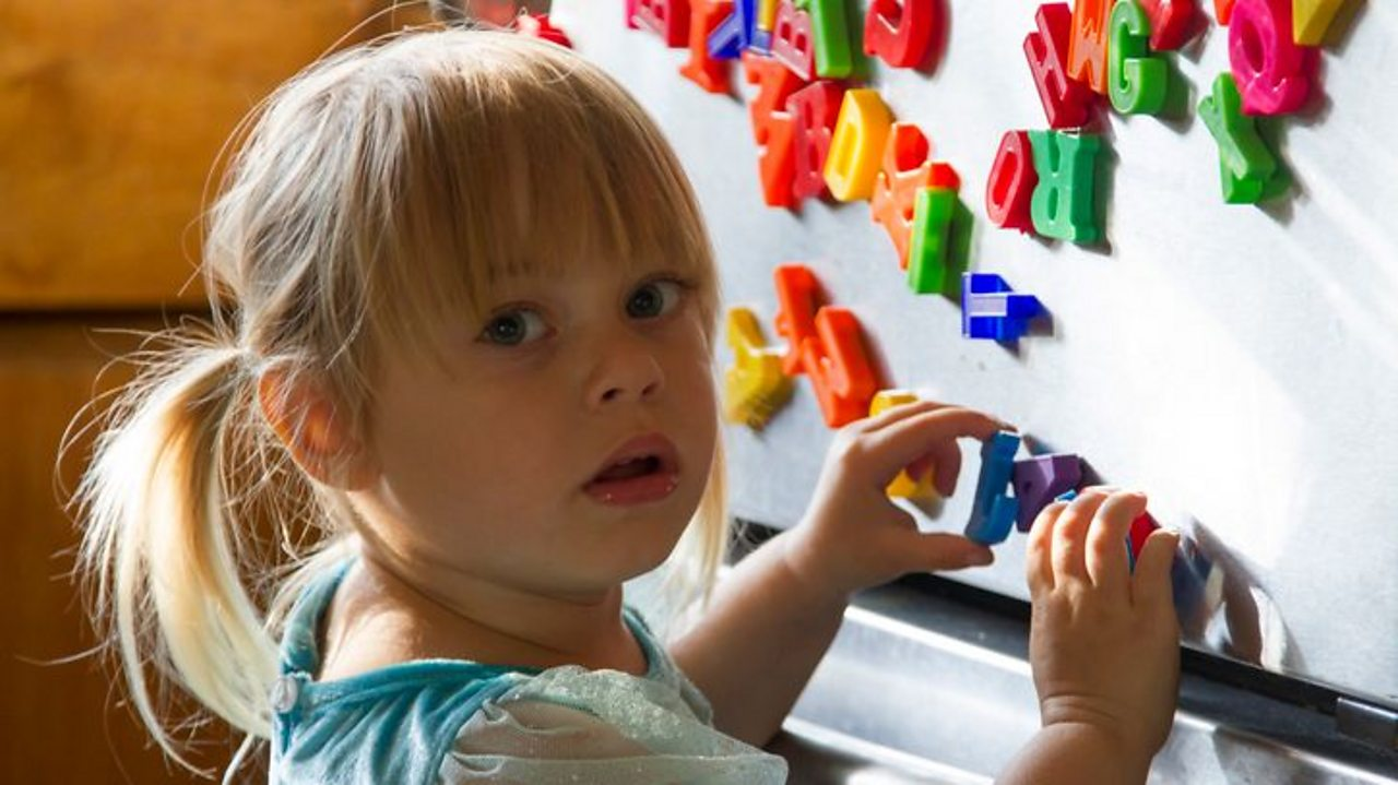 A toddler looks perplexed as she plays with alphabet fridge magnets.