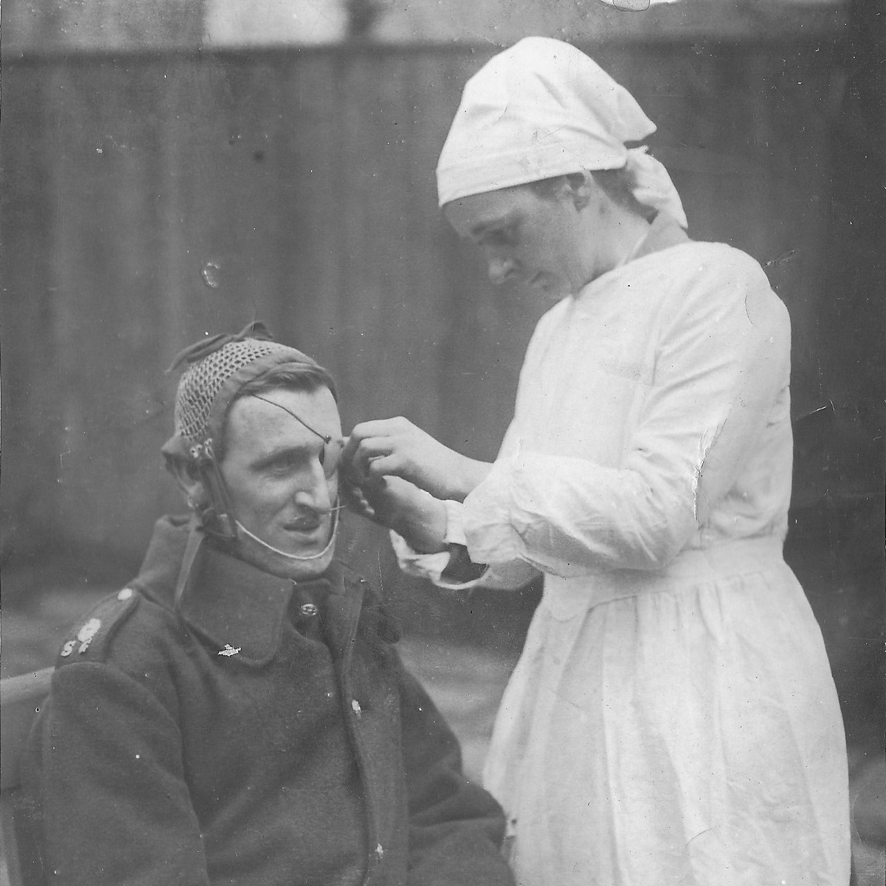 Photograph of Anne Acheson tending the eyepatch of a serviceman while working for the SRA
