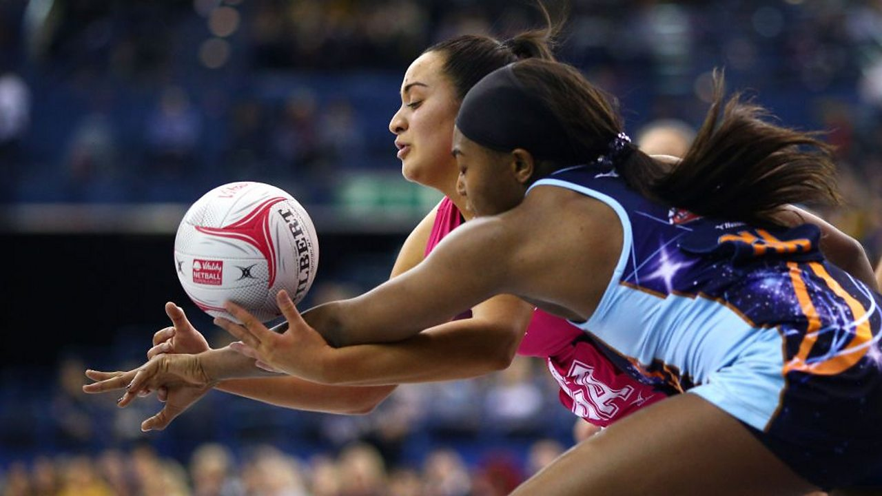 Two netball players running for the ball.