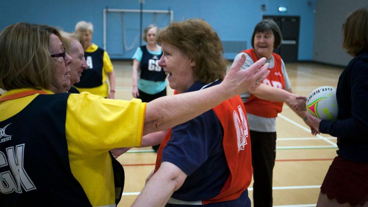 Two older women in netball kit hugging.