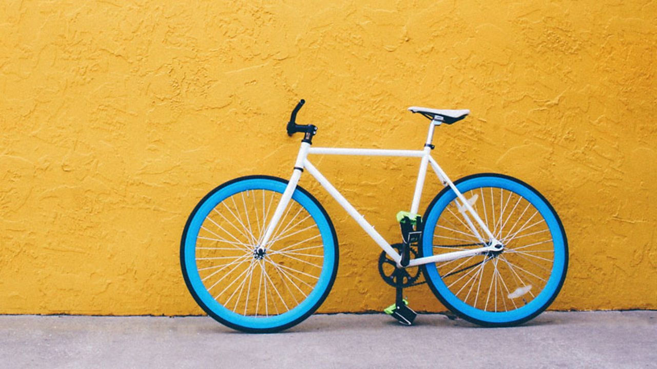 A picture of a bike leaning against a yellow wall