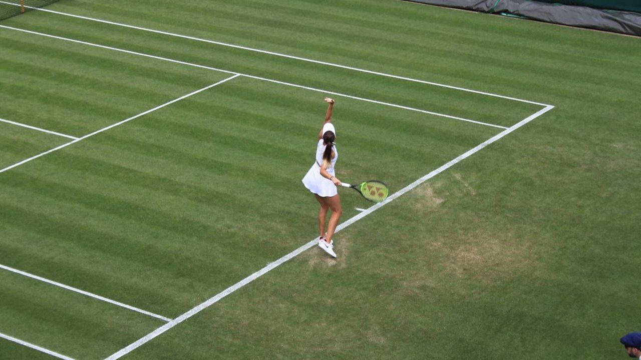 Tennis player serving at Wimbledon