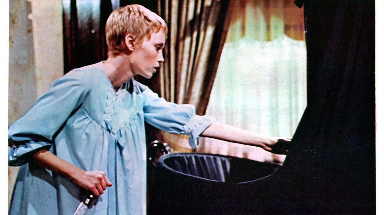 Mia Farrow as Rosemary in 'Rosemary's Baby' leans over a black crib.