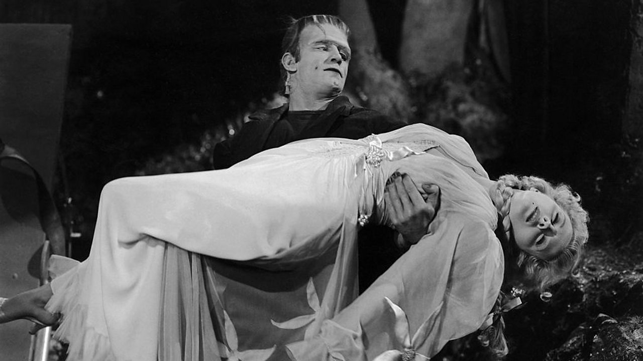 Frankenstein's monster holds a fainted damsel in his arms.