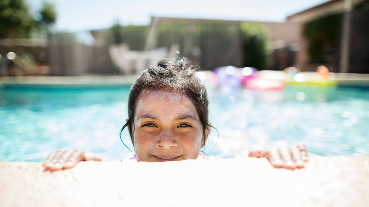Girl in swimming pool with sunscreen on her face.