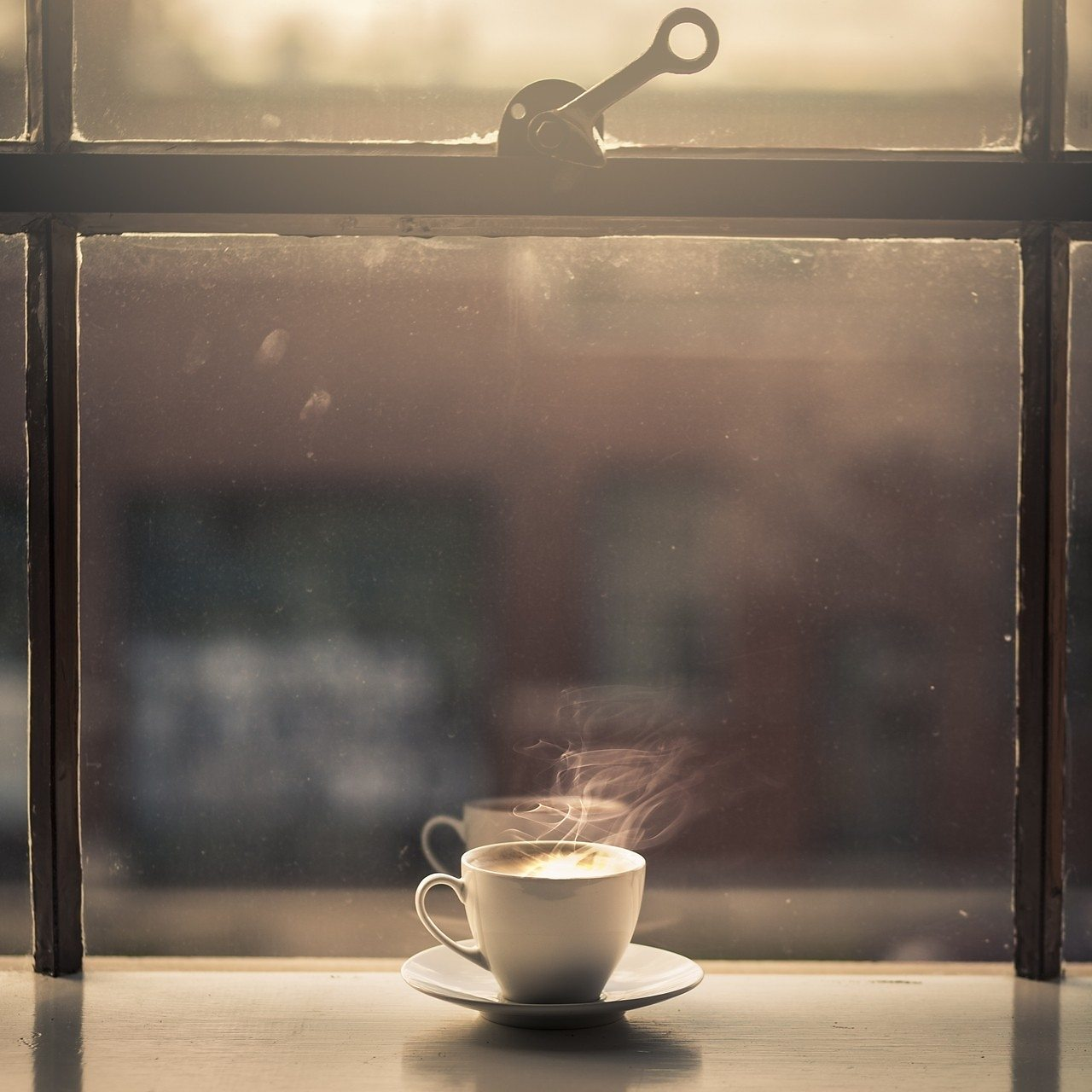 Hot cup of coffee in a sunny window.