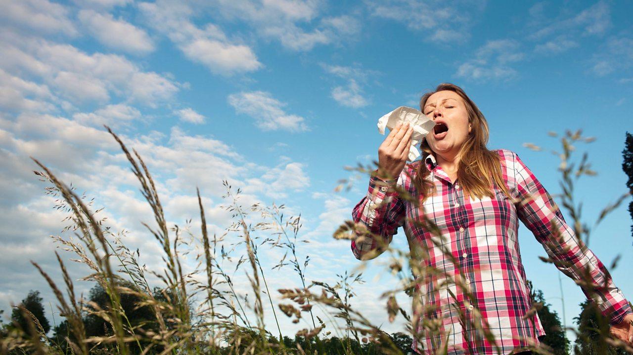 Women sneezing in a field.