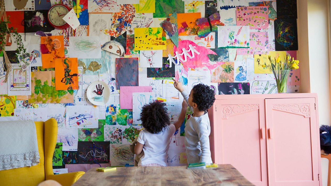 Siblings looking at artwork on wall