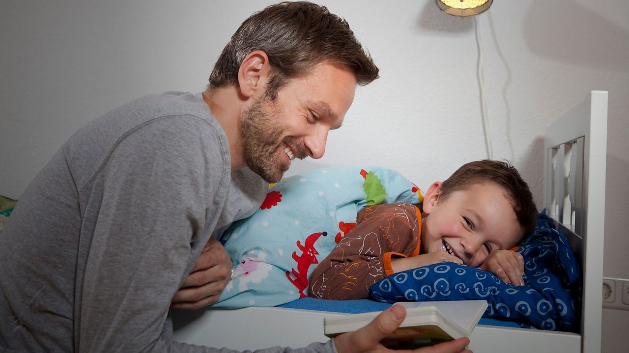 Father reading bedtime story to son
