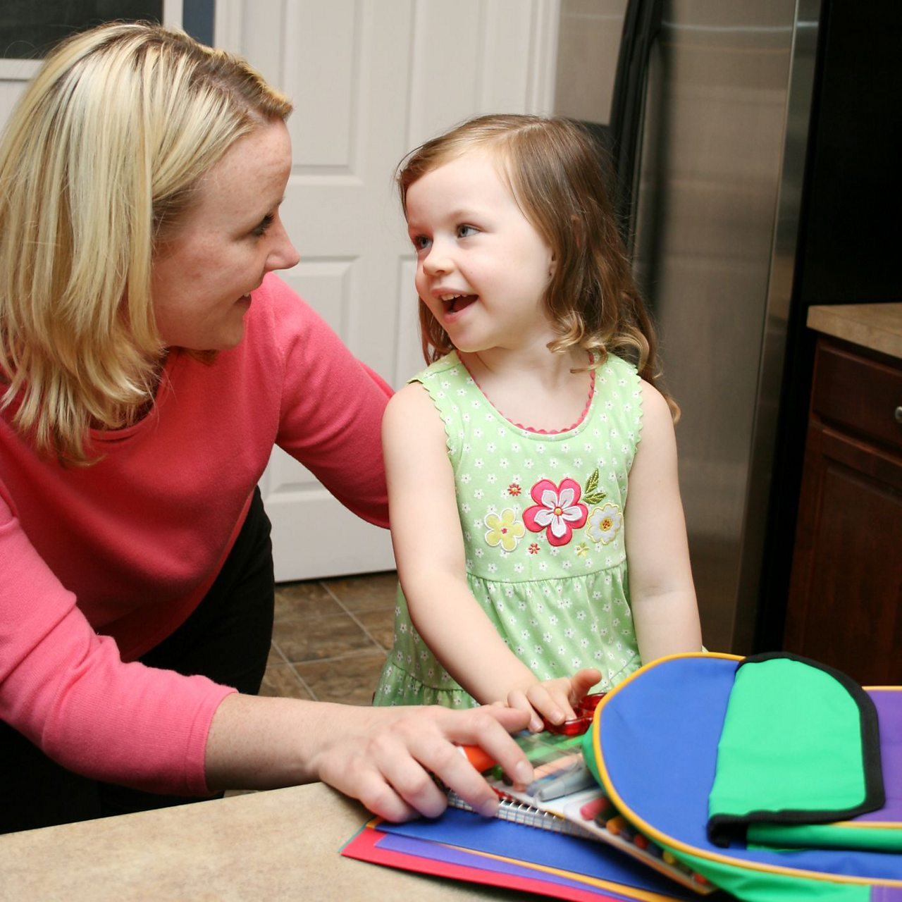 Mum packing schoolbag with daughter