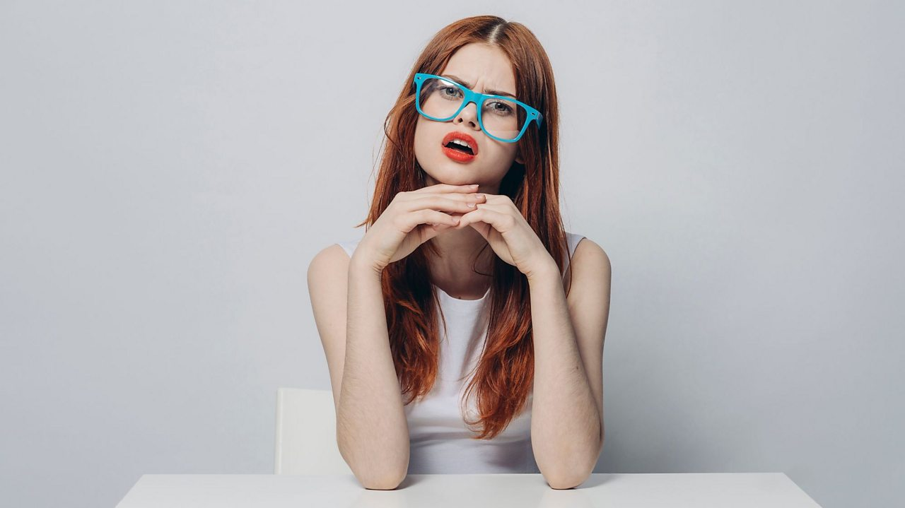 A redhead with with glasses stares from across the table as if interrogating the viewer.