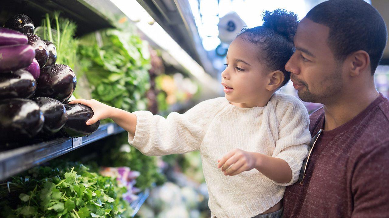 Child picking vegetables at supermarket