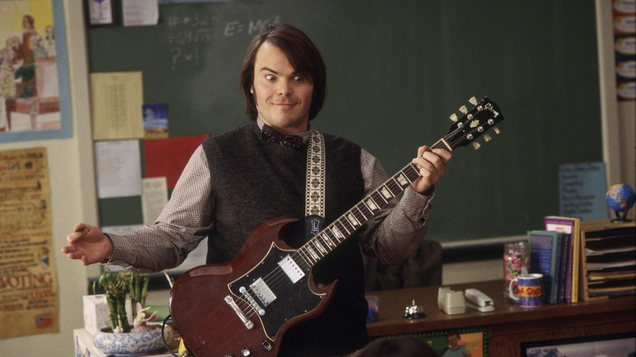 Jack Black as Finn Dewey in School of Rock. He is holding a guitar at the front of a classroom.
