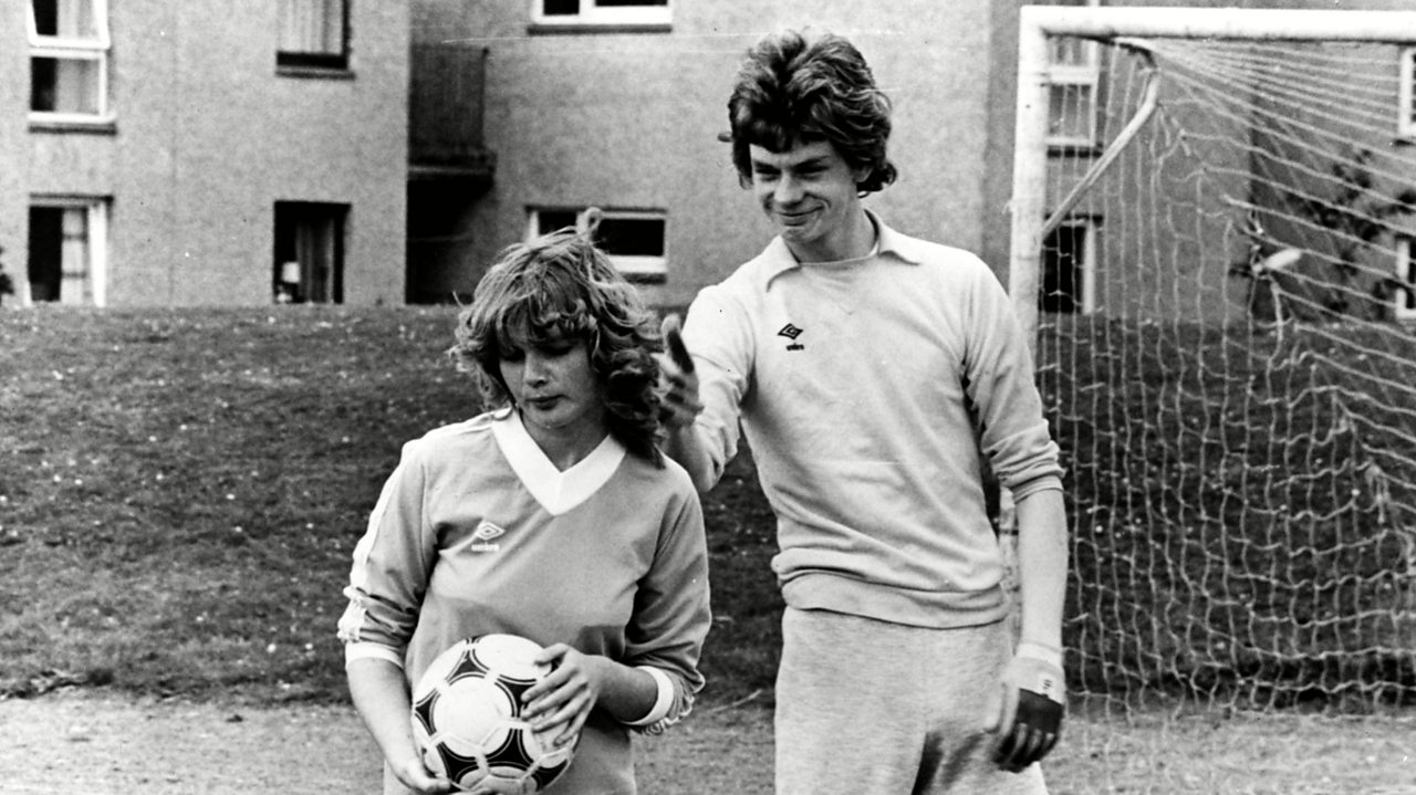 Dorothy and Gregory in Gregory's Girl, stood on a football pitch. Dorothy is holding a football and Gregory is giving a thumbs up behind her head.