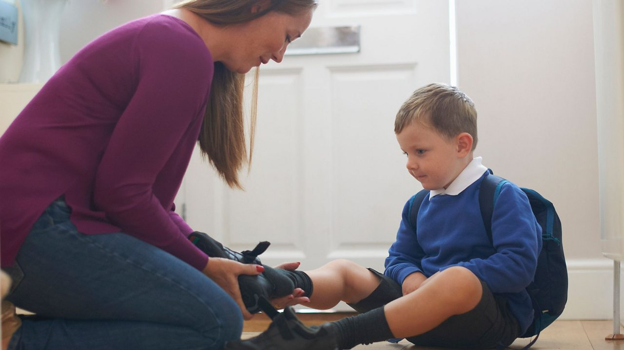 A mum putting her child's shoe on.